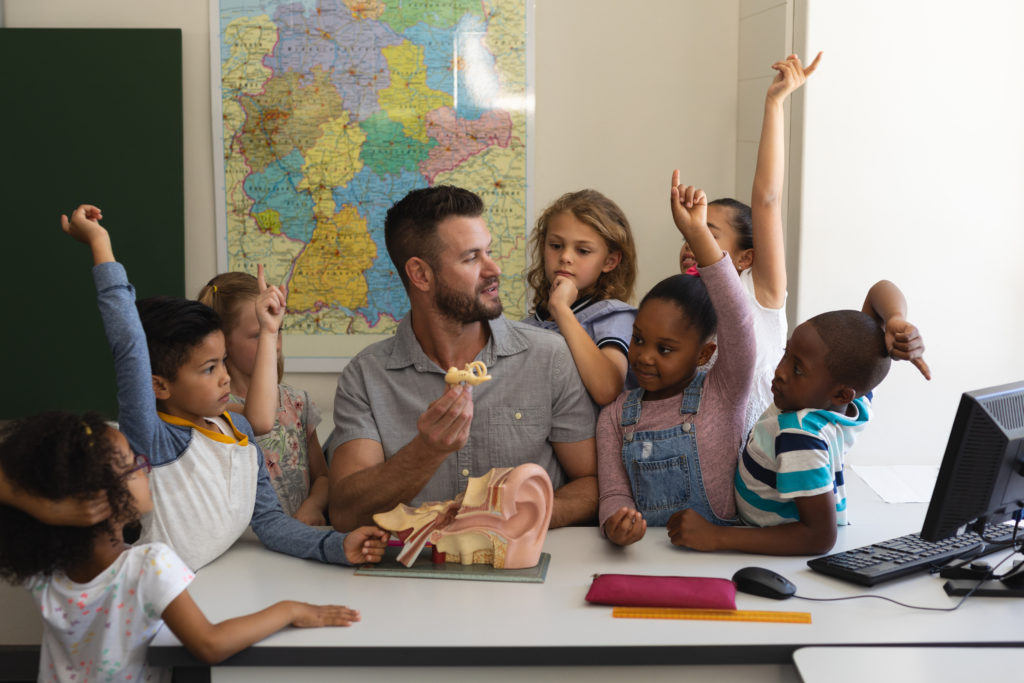 Front view of curious schoolkids raising hands around teacher teaching anatomy at desk in classroom of elementary school