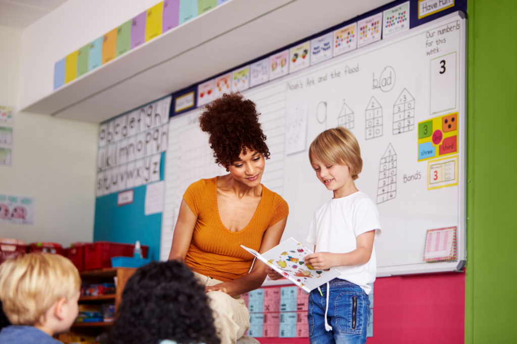 Male Pupil In Elementary School Classroom Reading Book To Class With Teacher