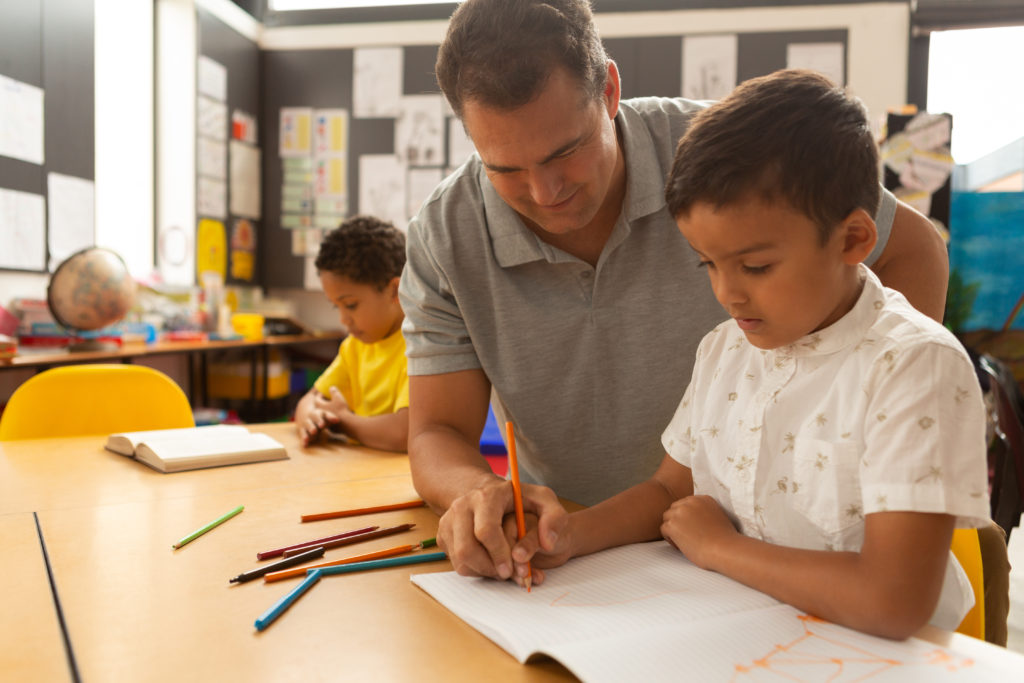 Front view of a handsome Caucasian male teacher teaching a mixed-race schoolboy to draw in a classroom at school
